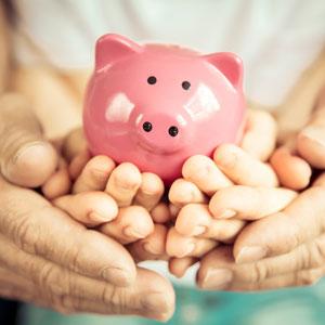 hands holding savings bank for wills and trustees